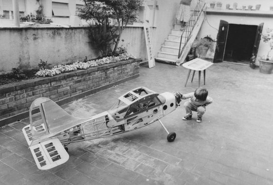 1950 Young boy playing with airplane model at home