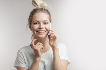 Beautiful smiling blond woman with hair bun talking by smartphone, flirting with her boyfriend, looking at camera with dreamy expression, isolated over white wall with copyspace. Closeup. Isolated.