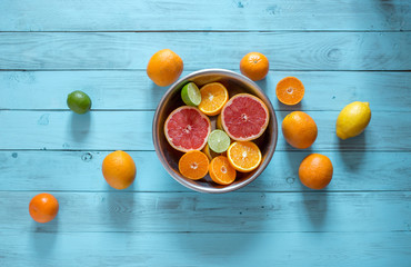 High angle shot of sliced fresh juicy oranges, mandarines, lemons in a bowl and some whole citrus fruits lying near the bowl on a blue wooden background with copyspace.