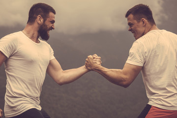 Strong male bodybuilders in white t-shirts greeting each other in wrestling manner outdoor over foggy mountain landscape. Rivalry, challenge, strength comparison concept Wall mural