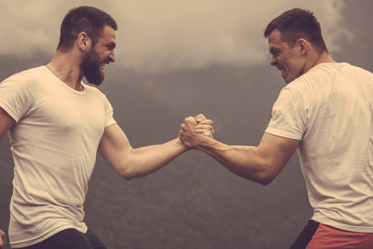 Strong male bodybuilders in white t-shirts greeting each other in wrestling manner outdoor over foggy mountain landscape. Rivalry, challenge, strength comparison concept