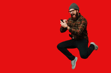 Bearded hipster man jumping over red background and using smartphone