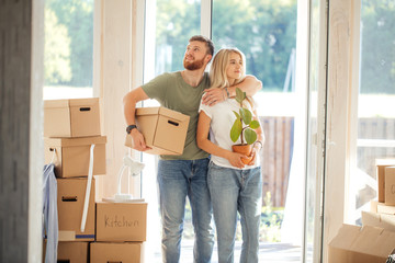 Smiling couple hold boxes in new home. Dreaming new home