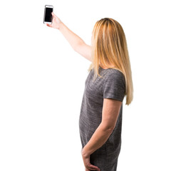 Middle-age blonde woman taking a selfie with the mobile on isolated white background