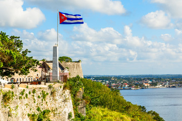 La Cabana Spanish fortress walls and Cuban flag in the foreground, with sea in the background, Havana, Cuba