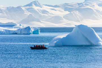 Foto auf AluDibond Antarktis Boat full of tourists passing by the huge icebergs in the bay near Cuverville island, Antarctic peninsula