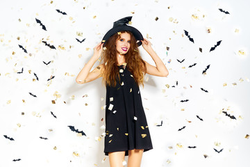 happy young woman in black witch halloween costume on party over white background with bats . firecrackers in the background. confetti . the concept of Halloween . funny face.