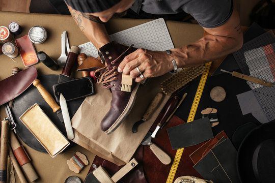 Enjoying process of creation custom made shoes. Workplace of shoe designer. Hands of shoemaker dealing with cobbler tool, close up