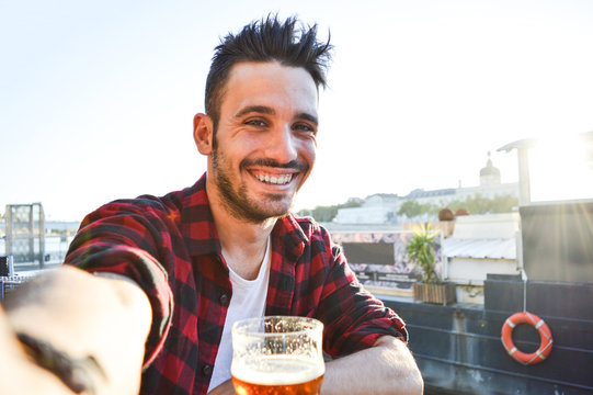Handsome man taking a selfie drinking a beer at the bar