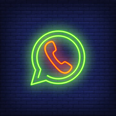 Messenger neon sign. Luminous signboard with red phone in green speech cloud. Night bright advertisement. Vector illustration in neon style for communication and exchanging messages