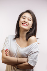 Asian smiling joyfully female with dark loose hair, dressed casually, looking with satisfaction at camera, being happy. Studio shot of appealing Korean woman isolated against blank wall.