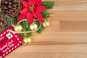 Christmas decoration - golden baubles, poinsettia, fir branches and cones on natural wooden background. Copy space on the right.