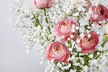 Pink ranunculus flowers and tiny white gypsophila paniculata.