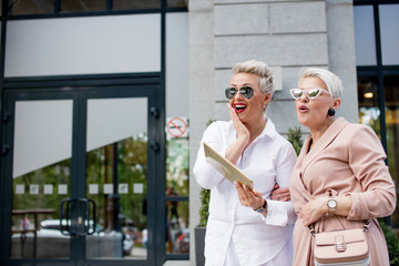 Two blond businesswoman walking on street near building. business woman going together with tablet computer and talking about projects