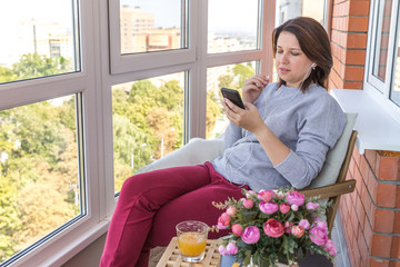 Young woman on a balcony listening music or talking by phone