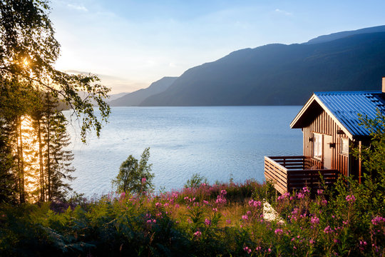 Wooden house with terrace overlooking scenic lake at sunset in Norway Scandinavia
