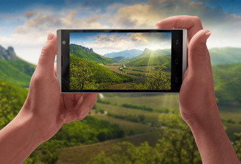 Majestic picture of mountain landscape on a screen of smartphone