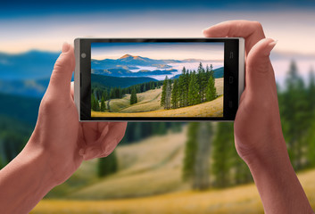 Panorama of Carpathian mountain valley on a screen of smartphone