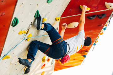 Sport man hanging extreme sport climbing wall in outdoor gym