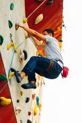 Muscular man practicing rock-climbing or lead climbing on an artificial rock wall