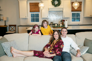 Mom and Dad on Couch in Living Room New Home with Kids Girls Behind Them