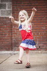Portrait of cheerful little girl dancing and playing outdoors