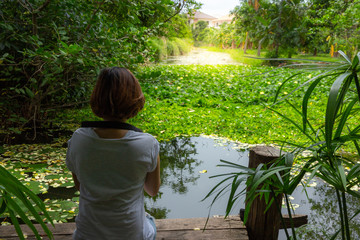 young woman sit on floor and looking at lotus on pond