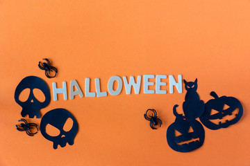 Halloween word with black cat and pumpkin and spider and skull on orange background.