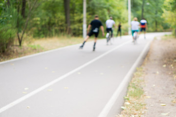 People rollerblading and Biking. Out of focus