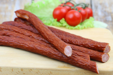 Traditional Polish smoked kabanos on wooden board, closeup