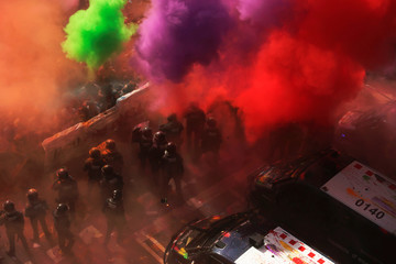 Separatist protesters throw coloured powder towards Mossos d'Esquadra police officers in Barcelona