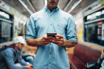 Man using phone in subway car, addicted people