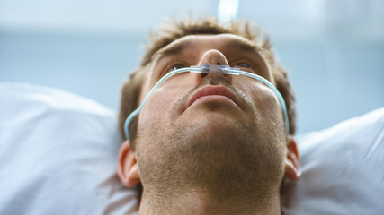 In the Hospital Sick Male Patient Lying on the Bed, He's Wearing Nasal Cannula to Help Him Breath. Terminally Ill Man.