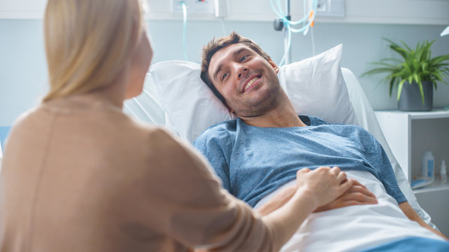 In the Hospital Sick Man Lying on the Bed, His Visiting Wife is Sitting Beside Him and Talking, Holding His Hands.