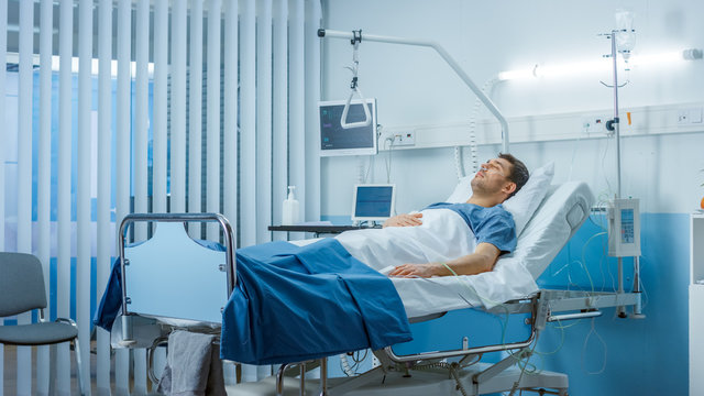 Sick Male Patient Lying on a Bed in the Private Ward in Hospital. White, Clean Environment.