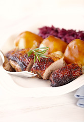 Duck breast with potato dumplings and red cabbage. Concept for a tasty and hearty dish. Bright wooden background.