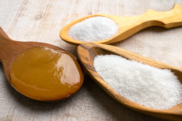 Artificial Sweeteners and Sugar Substitutes in wooden spoons. Natural and synthetic sugarfree food additive:  sorbitol, fructose, honey, Sucralose, Aspartame