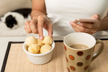 Woman picking bread cheese (known as Pao de Queijo in Brazil) and holding cell phone. Cup of coffee and comestic cat in the background.