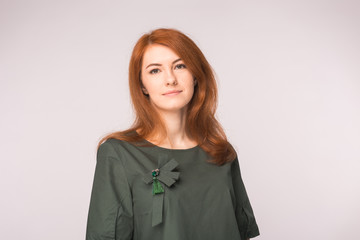 fashion, modeling and people concept - young red head woman standing over white background.
