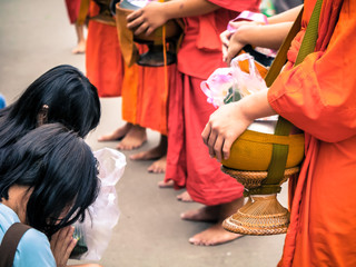 people give some food for monk in Thailand with dramatic tone