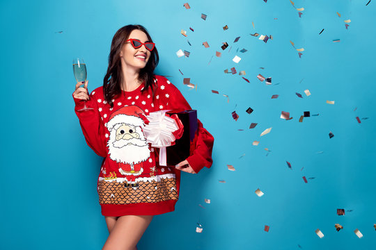 Pretty brunette woman in sunglasses and red pullover with Santa design standing under falling confetti with glass of champagne and gift box on blue background in studio. Isolate