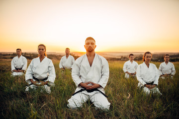 Karate group sitting on the ground and meditates