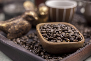 Coffee beans in a wooden Bowl on the wooden floor.