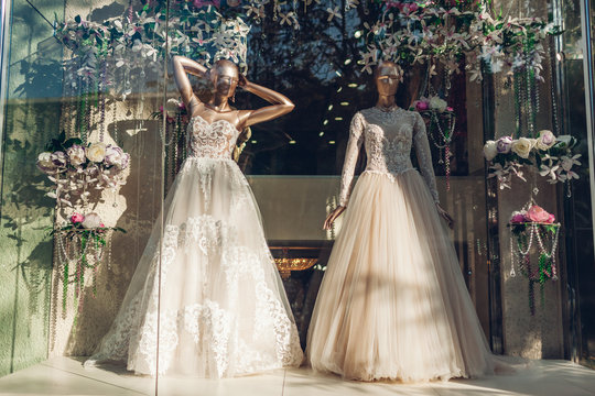 Collection of stylish wedding dresses on showcase of shop. Two mannequins wearing beautiful gowns on display