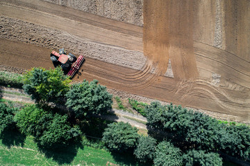 Wall Mural - Tractor harrownig the large brown field