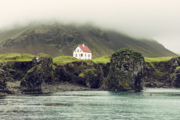 Printed kitchen splashbacks Coast Lonely icelandic house with red roof on the sea coast with green grass meadow, rocks anf foggy sky. Natural Iceland travel landscape.