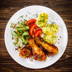 Grilled chicken drumsticks with boiled potatoes and vegetables
