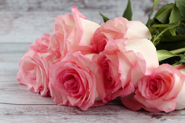 Beautiful bunch of pink roses lies on a light background.