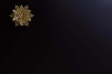 Golden snowflake ornament on the up-left corner of a black gradient background