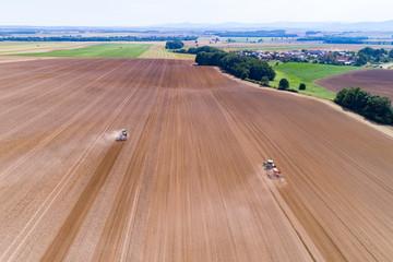 Wall Mural - Tractors harrownig the large brown field